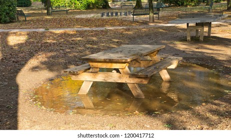 Picnic table in a puddle after heavy rain.