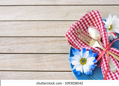Picnic Table Setting in Red White and Blue Colors for July 4th Celebration on Wood Board Background Table with room or space for copy, text or your words.  A horizontal flatlay photo from above view.