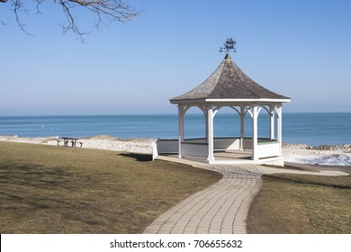 A picnic table sits beside a white gazebo in Queen's Royal Park in Niagara on the Lake Ontario Canada.