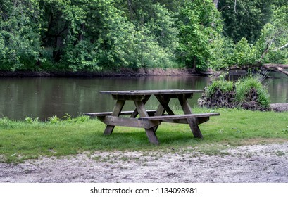 A picnic table sits ready for campers along a calm river side in a beautiful rural park