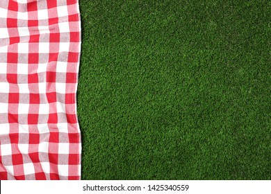 Picnic tablecloth on grass, top view. Space for text