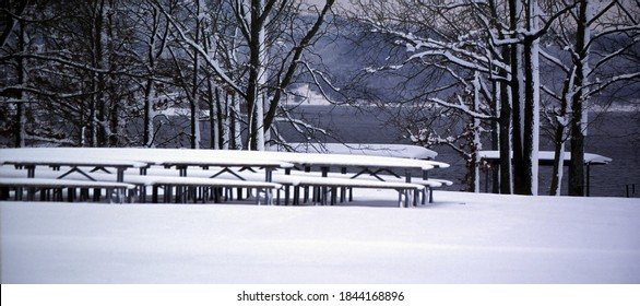 Picnic Tables covered in snow are a reminder of summer days that seem long ago at a recreation area on Beaver Lake in northwest Arkansas.