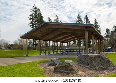 Picnic tables under wood shelter structure in suburban neighborhood city park