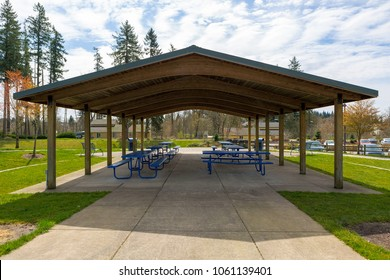 Picnic tables under wooden roof shelter structure in suburban neighborhood city park