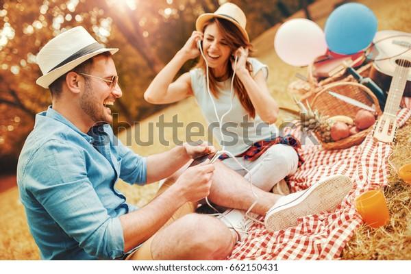 ピクニックの時間。公園でのピクニックで音楽を聴いている若い夫婦が、一緒に楽しむ。愛と優しさ、デート、恋愛、ライフスタイルのコンセプト