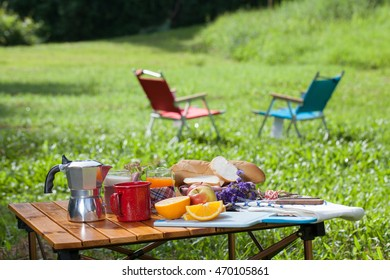 picnic, view of picnic table with various fruits, juice, pancake, coffee  at the camping area.