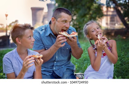 Picnic.Father with children eating pizza.