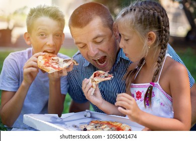Picnic.Father with children eating pizza