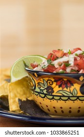 Pico De Gallo in an Ethnic bowl with chips against a neutral background