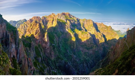 Pico do Arieiro mountains lit by sunset, hiking above the clouds. Mountain trails in Madeira island. Pico Arieiro-Pico Ruivo Hike. Scenic view of steep and beautiful mountains. Madeira, Portugal.