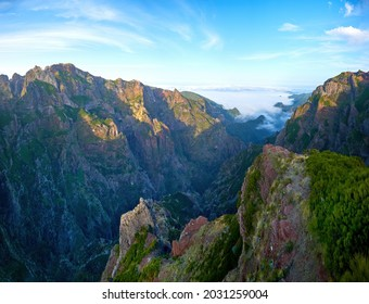 Pico do Arieiro mountains lit by sunset, hiking above the clouds. Mountain trails in Madeira island. Pico Arieiro-Pico Ruivo Hike. Panoramic view of steep and beautiful mountains. Madeira, Portugal.