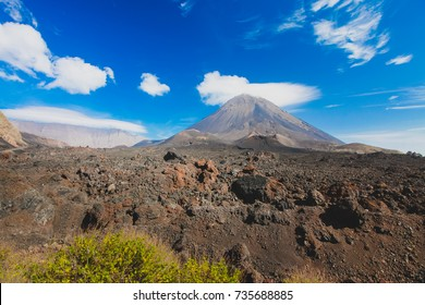 Pico do Fogo, volcano on the island of Fogo on Cabo Verde islands, with some grass and rocks in the foreground.