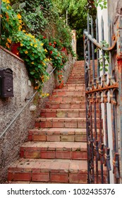 Picruresque red brick stairs with rusty iron railing and vintage post box at one of many labyrinth narrwo streets on Capri island, Italy.