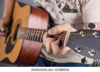 A picture of an acoustic guitar, classical color, in the hands of a guitarist with a clamped chord. Both hands in the frame