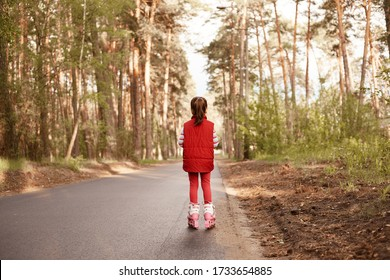 Picture of active energetic little girl wearing red suit, rollerskating during holidays, enjoying nature, breathing fresh air, being alone on road, spending time in forest, standing back to camera.