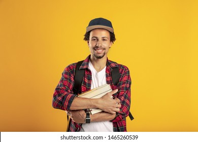 Picture of adult latino student over yellow background. Hold book in hands and smile. Standing alone. University time