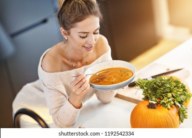 Picture of adult woman tasting pumpkin soup in the kitchen