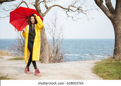 Picture of amazing african curly young lady wearing yellow coat holding umbrella walking outdoors. Looking at camera.