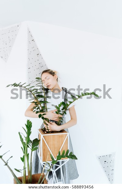 Picture of amazing young asian lady posing over white wall with plants. Eyes closed.
