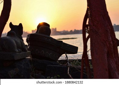Picture of ancient shivling with statue of bull in the old city of India, there is beautiful sunset in the background