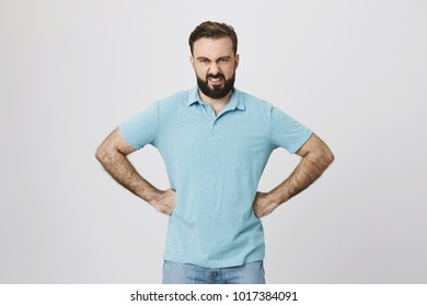 Picture of an angry bearded man holding his arms on waist. Body language and emotions concept. Male is fed up of his neighboor dog who always barks at night so he went to argue.
