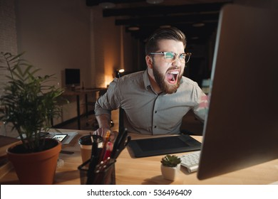 Picture of angry web designer dressed in shirt and wearing eyeglasses working late at night and looking at computer while screaming.