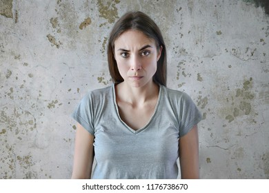 Picture of angry young woman standing isolated over concrete background