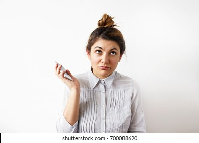 Picture of annoyed young secretary with hair knot dressed in blouse rolling her eyes while having annoying phone conversation, holding mobile phone away from her ear, not listening to interlocutor