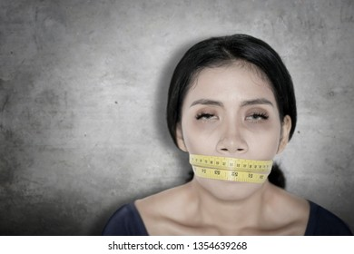 Picture of Asian anorexia woman covering her mouth with a measure tape