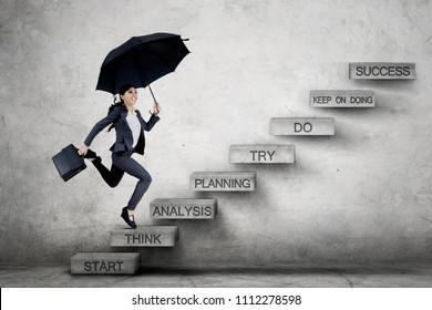 Picture of Asian business woman carrying a suitcase and umbrella while running on the staircase with a strategy plan toward success