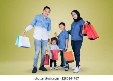 Picture of Asian family holding shopping bags while standing in the studio with golden color background