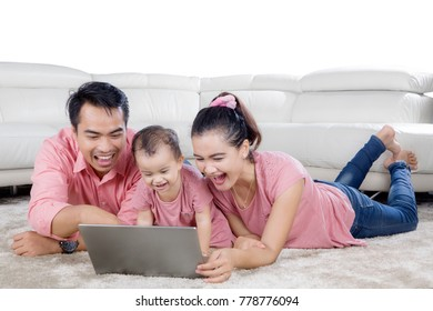 Picture of Asian family laughing together while using a laptop and lying on the carpet