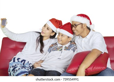 Picture of Asian family wearing Santa Claus hat while taking a selfie photo with a smartphone, isolated on white background