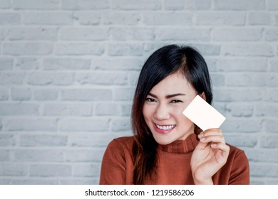 picture of Asian girl smiles as she holds the card.