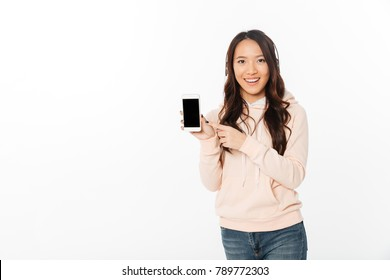 Picture of asian happy woman standing isolated over white background listening music with headphones showing display of mobile phone.