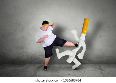 Picture of an Asian obese man wearing sportswear while kicking a cigarette. Quit smoking concept.
