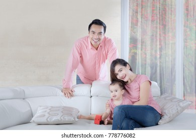 Picture of Asian parents smiling at the camera while playing with their daughter at home