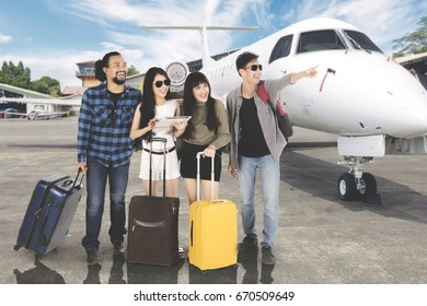 Picture of Asian woman holding a digital tablet while standing with her friends near an airplane at the airport
