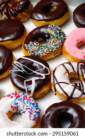 Picture of assorted doughnuts with chocolate frosted, pink glazed and sprinkles donuts.