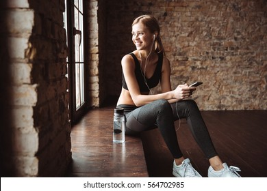 Picture of attractive fitness woman sitting in gym while using phone and listening music with earphones.