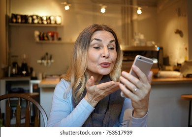 Picture of attractive mature woman holding mobile phone and blowing kiss while having video chat with her daughter, sitting in kitchen. Beautiful senior female posing at home, taking selfie