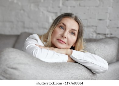 Picture of attractive middle aged Caucasian woman with long straight hair resting on grey comfortable sofa, having sad unhappy expression, feeling bored or lonely. People, lifestyle and age concept