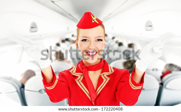 A picture of an attractive stewardess showing emergency exits in a plane