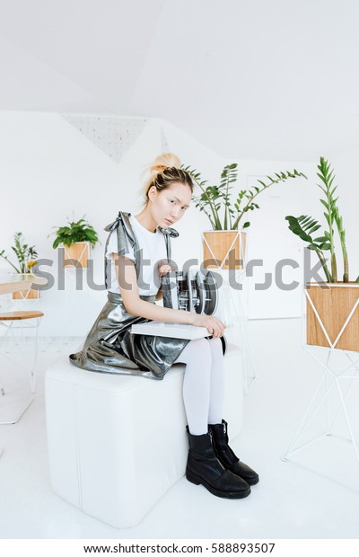 Picture of attractive young asian lady posing over white wall with plants. Looking at camera holding book.