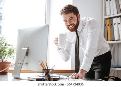 Picture of attractive young businessman dressed in white shirt standing in office while drinking tea and using computer.