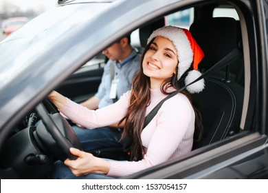 Picture of attractive young woman sit on driver's place. Hold hands on steering wheel and smile. Christmas or new year time. Wear red hat and smile. Man sit beside.