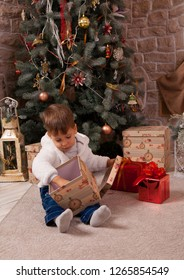 Picture of baby boy sitting near christmas tree with box