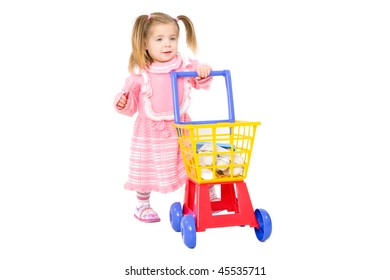 Picture of a baby girl pushing toy shopping trolley on a white background