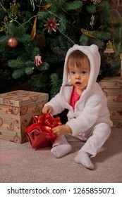 Picture of baby girl sitting near christmas tree with box