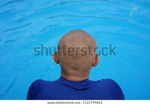 A picture of bald man waiting to dive in the swimming pool. Hair loss is common in Malaysia due to eating